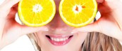 Beautiful blond  woman holding orange slices over white