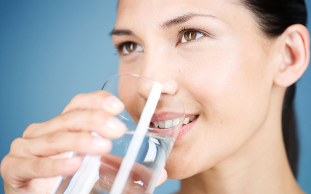 A young woman drinking a glass of water. Image shot 2006. Exact date unknown.