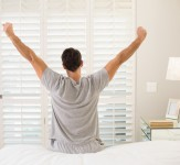 Rear view of a young man waking up in bed and stretching his arm