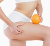 Woman squeezes cellulite skin on thigh as she holds orange