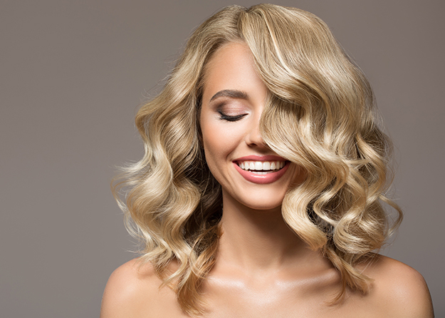 Blonde woman with curly beautiful hair smiling on gray backgroun