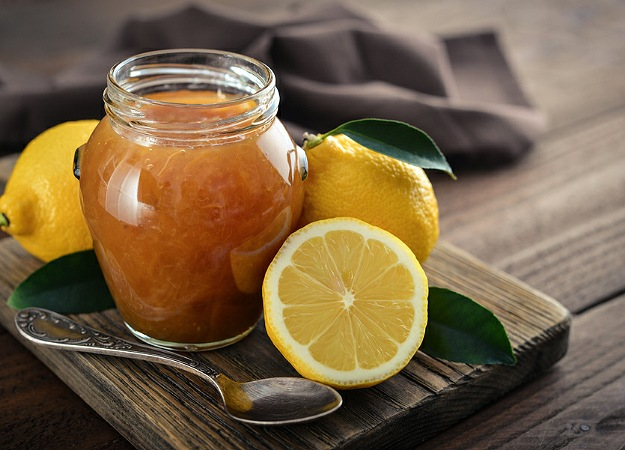 Lemon jam in jar with fresh lemons on wooden background closeup