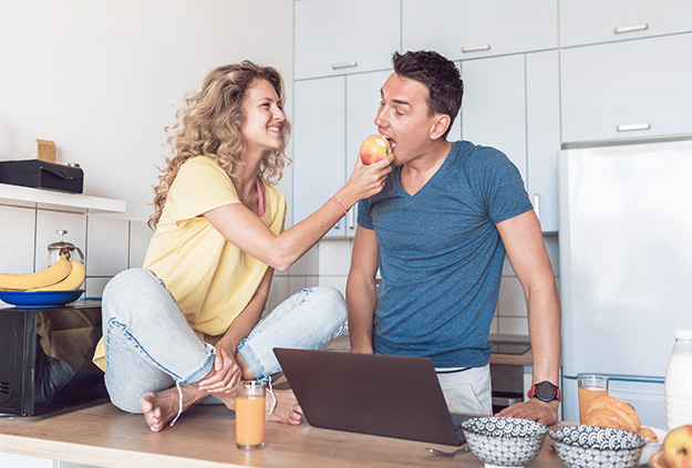 young attractive couple of man and woman cooking breakfast together in morning at kitchen